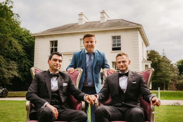 Daragh Doyle from Rainbow weddings with two same-sex grooms in tuxes in front of a white house