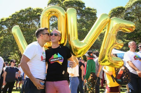 "Two men kiss in front of balloons that spell out ""LOVE"""