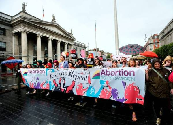 Volunteer group Abortion Rights campaign march down O'Connell Street with banner which states