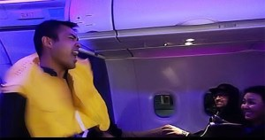 A flight attendant with an inflatable life vest around his neck dances and sings down the aisle of a plane watched by smiling passengers
