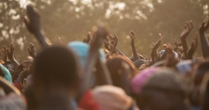 The hands of a crowd of Tanzanian people reaching for aid