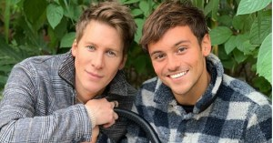 Tom Daley and Justin Lance Black sitting together outside.