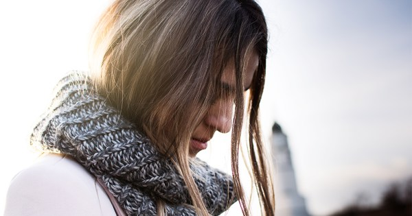 A woman after a break-up, looking down, hair hanging in her face