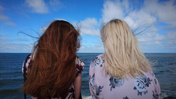Two girls looking out to the sea