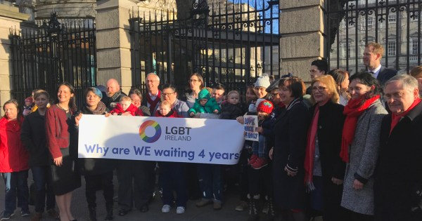 """LGBT families demonstrating outside Leinster House holding up a sign that reads, """"Why are we waiting 4 years?"""""""