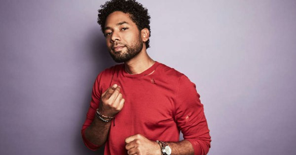 Jussie Smollett poses against a purple backdrop