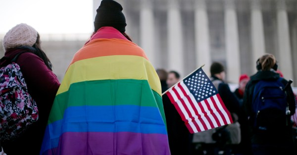Person in Washington DC with a rainbow flag over their back, holding an American flag