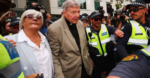 Cardinal George Pell is escorted by police.
