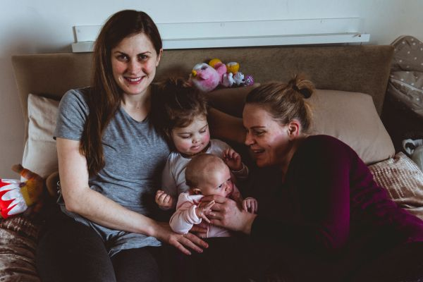 Female same sex parents on the couch at home, their toddler daughter in the middle holding her newborn sister