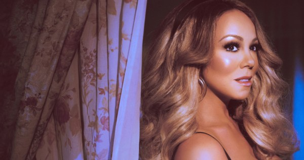 Image of Mariah Carey standing against a curtain.