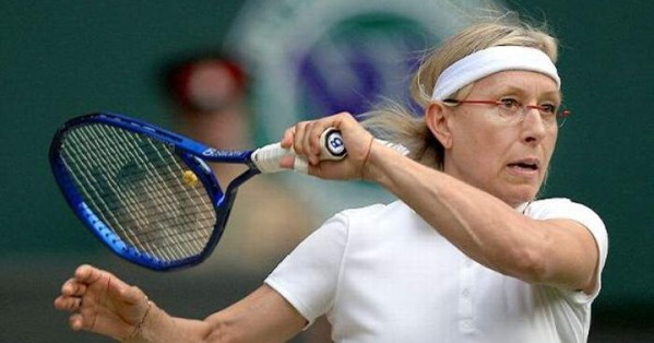 Tennis player Martina Navratilova in a white uniform while serving a ball