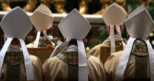 A group of priests at mass seen from behind