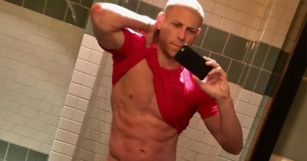 Amateur porn star BigCMen taking a bathroom selfie while lifting his top