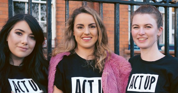 Three women wearing ACT UP t-shirts standing beside a fence