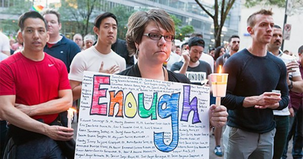 """People at a vigil, a woman is holding a sign which reads """"Enough"""", demanding demanding hate crime legislation"""