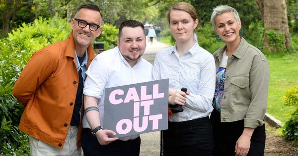 Four people hold a Call It Out' sign. They are a man, a woman, a trans man and a trans woman. they are standing in a park.