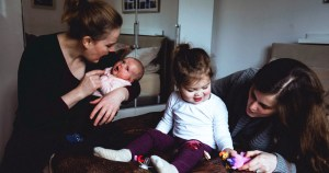 Two women at home with their daughters, one a baby in arms and the other a toddler playing on the couch, one of the many same-sex families in Ireland