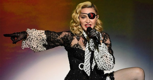 Pop star Madonna performing on stage, wearing an eyepatch and pointing to her right