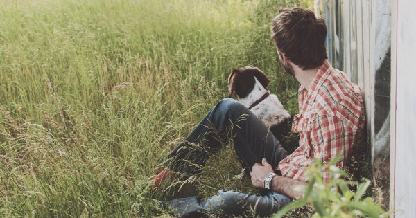 A young man and a dog in rural Ireland leaning against a wooden building in long grass looking away from the camera