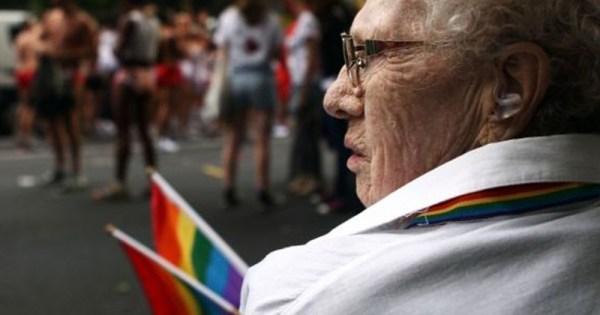 older woman holds pride flag