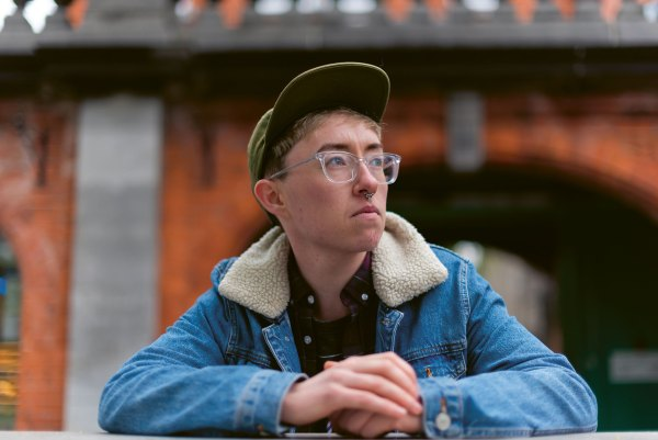 Non binary person wearing a baseball cap and glasses: in this piece queer people describe the difficulties of a simple trip to the barbershop