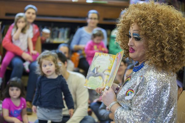 A drag queen spreading inclusive stories to a group of children and parents