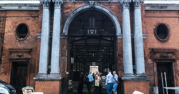 The exterior of the Fruit and Vegetable Market, a Victorian building. A few traders stand by the high arched door.