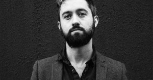 Villagers frontman Conor O'Brien with a beard posing moodily against a wall