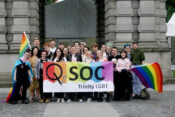 Members of Trinity's QSoc stand with QSoc sign