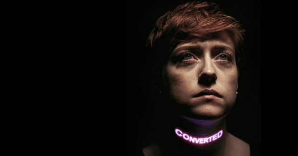 A woman in the shadows with the word Converted in lights across her neck