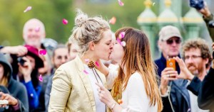 Wedding at Extinction Rebellion demonstration: Two women kissing while the crowd cheers behind them and rose petals are thrown in the air.