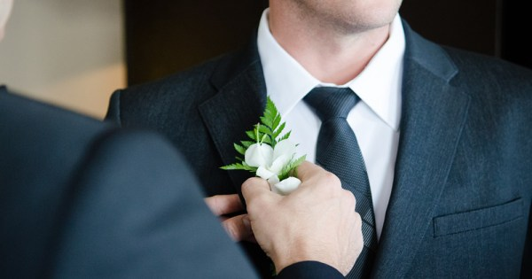 Same-sex marriage of two men both in suits with one man placing a wedding ring on the another's hand