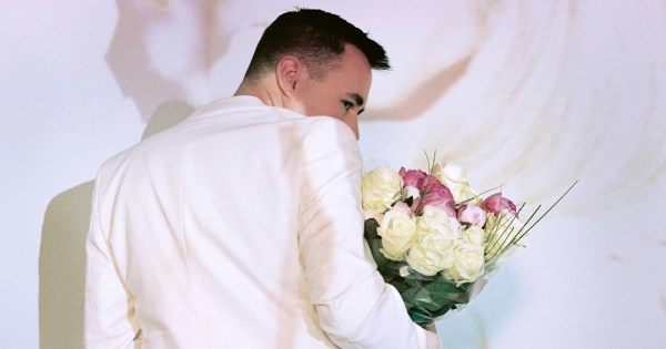 David Turpin - a man in his thirties holds a bouquet peering over his shoulder, his lower face hidden