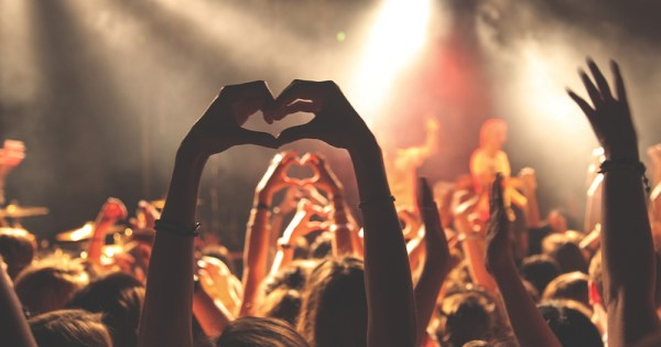 A live music gig with hands held in the air making a heart shape