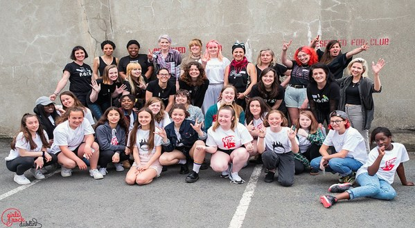A group of teenage girls and non-binary people sitting or standing in front of a grey wall wearing Girls Rock Dublin t-shirts and looking happy.