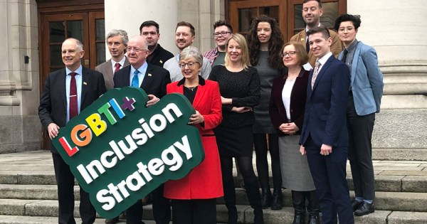 Minister Stanton and Minister Flanagan and other representatives holding a LGBT+ Inclusion Strategy sign