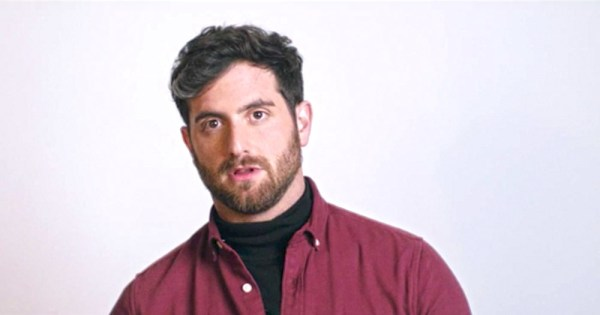 Image shows a bearded white man gazing to the left of the camera agains a white background, wearing a red shirt.