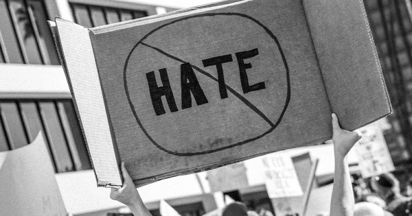 Hands holding a cardboard sign with the word Hate crossed out