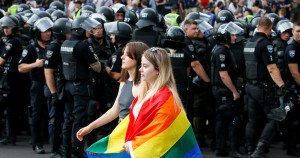 Two women walking in front of police officers, one of them wearing a rainbow flag. A bisexual woman has called for an investigation into torture in Chechnya.