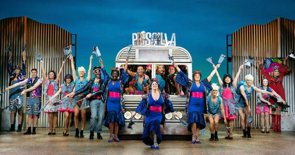 Cast of musical Priscilla Queen of the Desert standing in front of the iconic bus