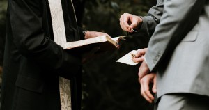 A priest performs a marriage ceremony and two men in grey suits stand before him holding a ring. none of their heads are visible