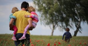 queer dad surrogacy Man carries his two daughters through field. His sun is running in the background. gay dad, surrogacy
