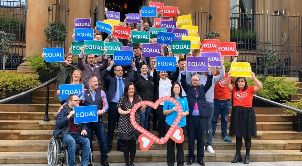 People holding EQUAL signs after same sex weddings in Northern Ireland became legal