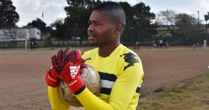 South Africa's first openly gay soccer player Phuti Lekoloane wearing a yellow jersey and holding a ball.