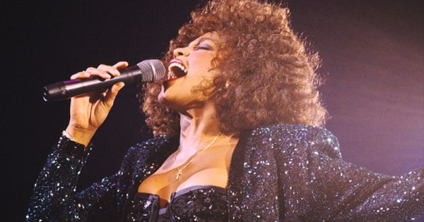 Whitney Houston signing into a microphone wearing a black sparkling jacket and dress, her songs will be played during Whitney Houston: Hologram Tour