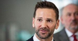 Aaron Schock in a black suit with stubble.