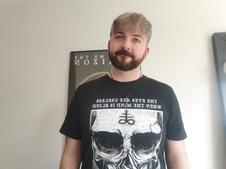 A man with a beard and pierced nose wearing a heavy metal style t-shirt