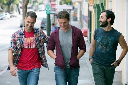 Three men walk down a city street, chatting and smiling