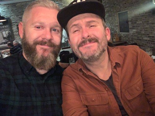 Two bearded smiling men with their heads together