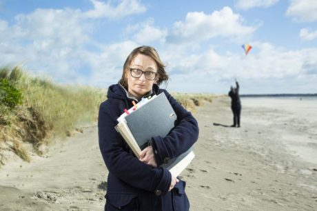 A woman wearing glasses holds a bundle of files while standing on a beach
